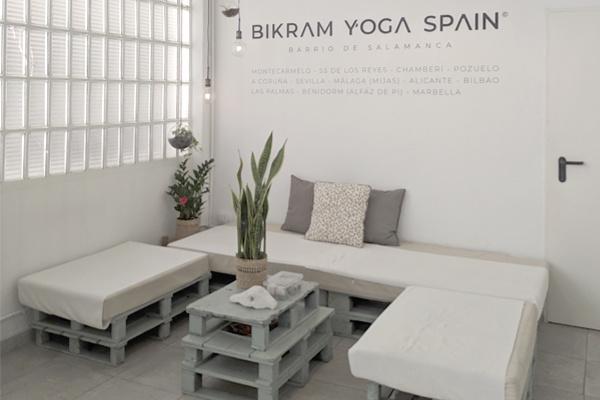 Instalaciones Bikram Yoga Barrio Salamanca, zona de descanso, sofá y mesa, decoración en blanco